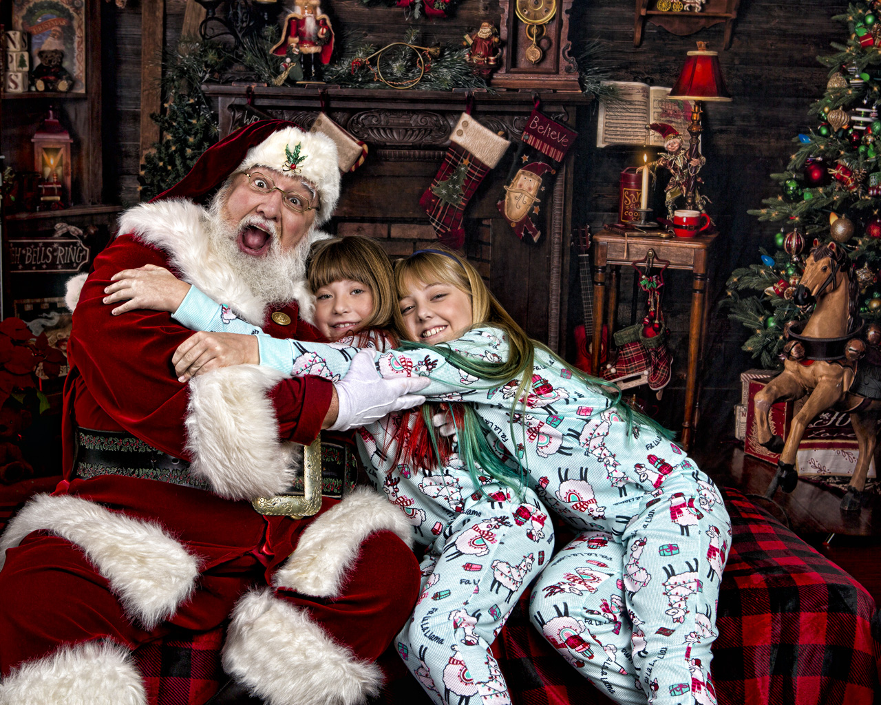 Santa having a great time laughing and posing with two girls in the Santa Experience Studio